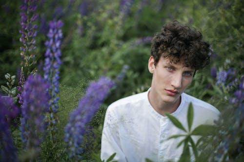 Man in White Dress Shirt Standing Near Purple Flower Field