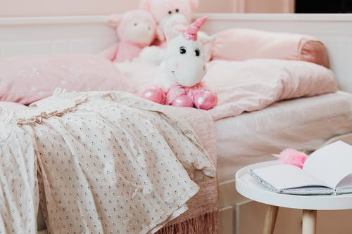 Pink and White Hello Kitty Plush Toy on Bed