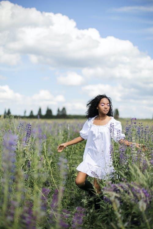 Girl in White Dress Standing on Purple Flower Field