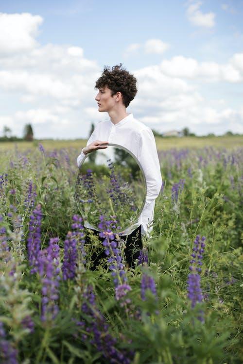 Woman in White Long Sleeve Shirt Standing on Purple Flower Field