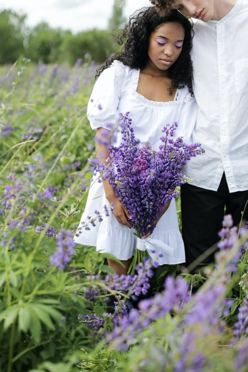 Woman in White Shirt and Black Pants Holding Purple Flowers
