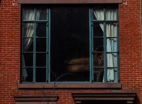 Exterior of aged red brick building with big glass window with curtains and dry flower on windowsill in daylight