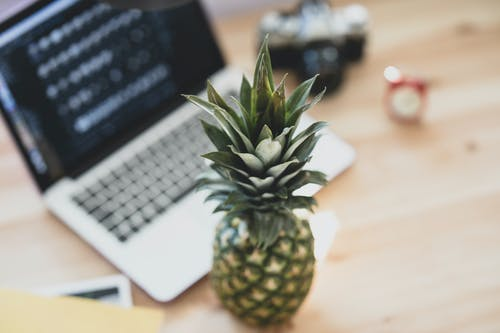 Green Pineapple Fruit Beside Silver and White Computer Keyboard on Brown Wooden Table