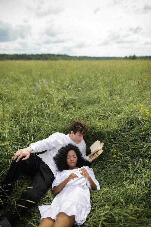 Man in White Dress Shirt Lying on Green Grass Field Reading Book