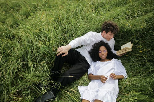 Man in White Dress Shirt Lying on Green Grass Field
