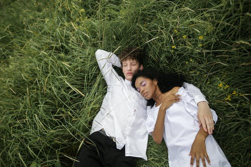 Woman in White Dress Shirt Lying on Green Grass