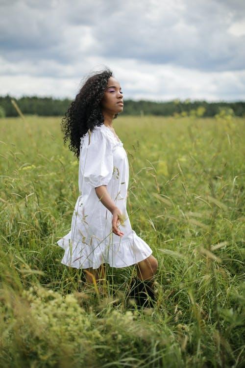 Girl in White Dress Standing on Green Grass Field