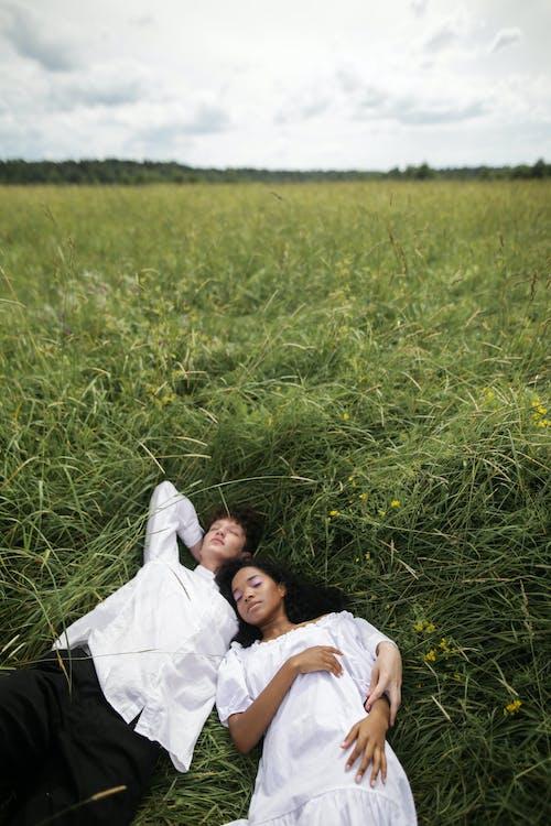 Woman in White Dress Lying on Green Grass Field