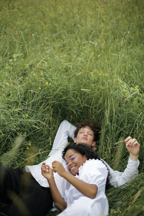 Man and Woman Lying on Green Grass Field