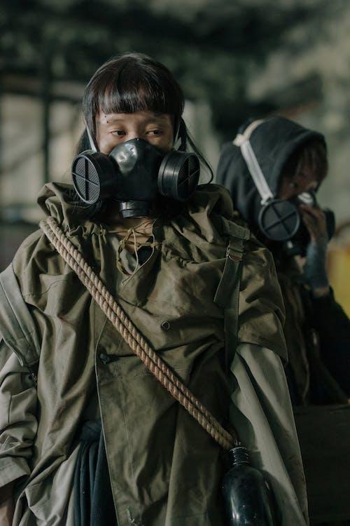 Man in Green Jacket Wearing Black Gas Mask