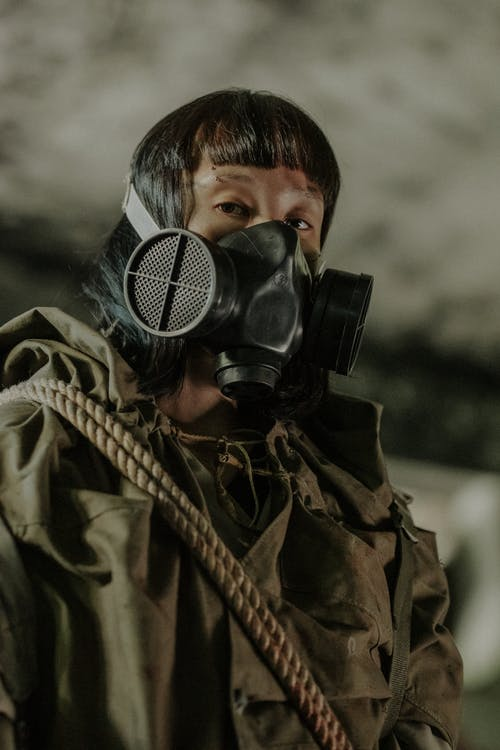 Person Wearing Black Gas Mask and Brown Jacket