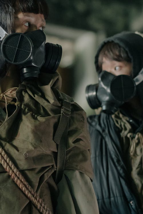 Person in Green and Brown Camouflage Jacket Wearing Black Gas Mask