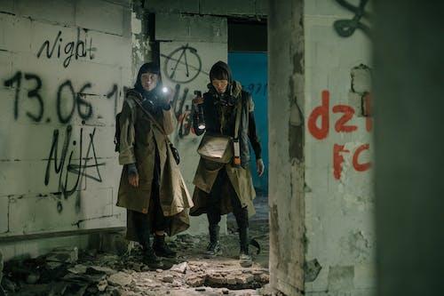 Man in Black Jacket Standing Beside Woman in Brown Coat