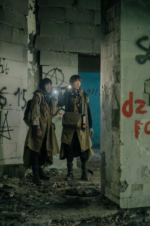 2 Men in Brown Coat Standing Beside White Wall
