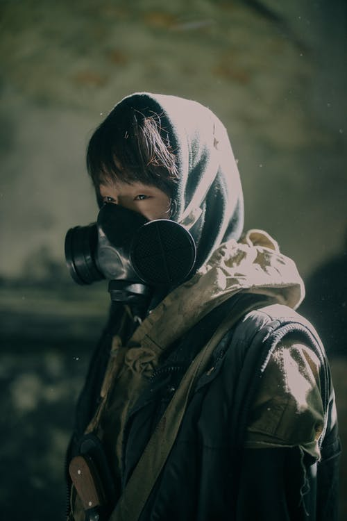Person in Black and White Hoodie Wearing Black Gas Mask