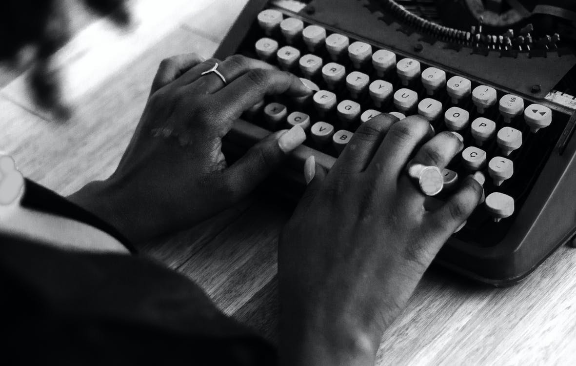Grayscale Photo of Persons Hand on Typewriter