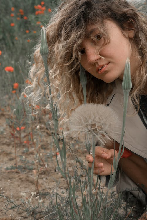 Woman in Brown Fur Coat Holding White Dandelion Flower