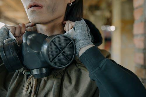 Woman in Black Leather Jacket Wearing Black Gas Mask