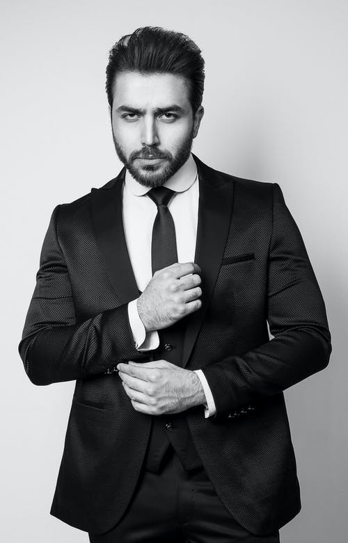 Black and white of bearded pensive strict male with trendy hairstyle in tie and formal outfit looking at camera