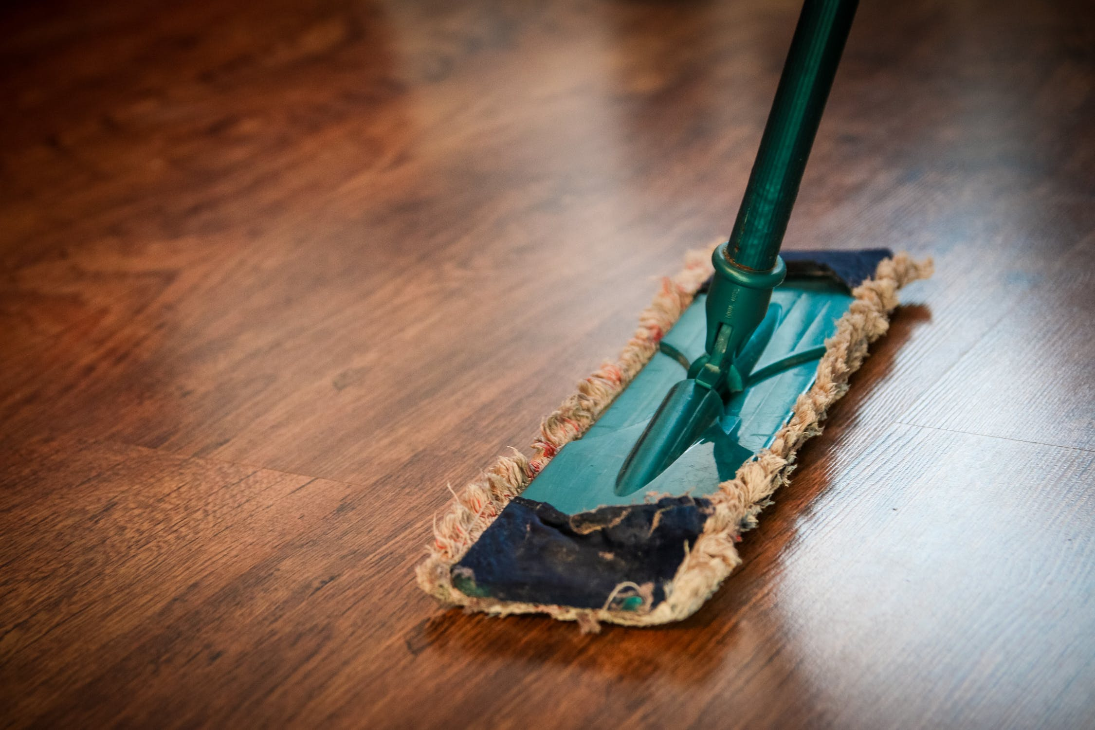 A swiffer mopping a wooden floor