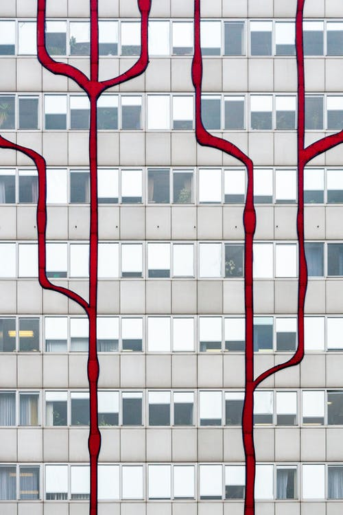 Bright red lines painted outside facade of contemporary high rise building on city street