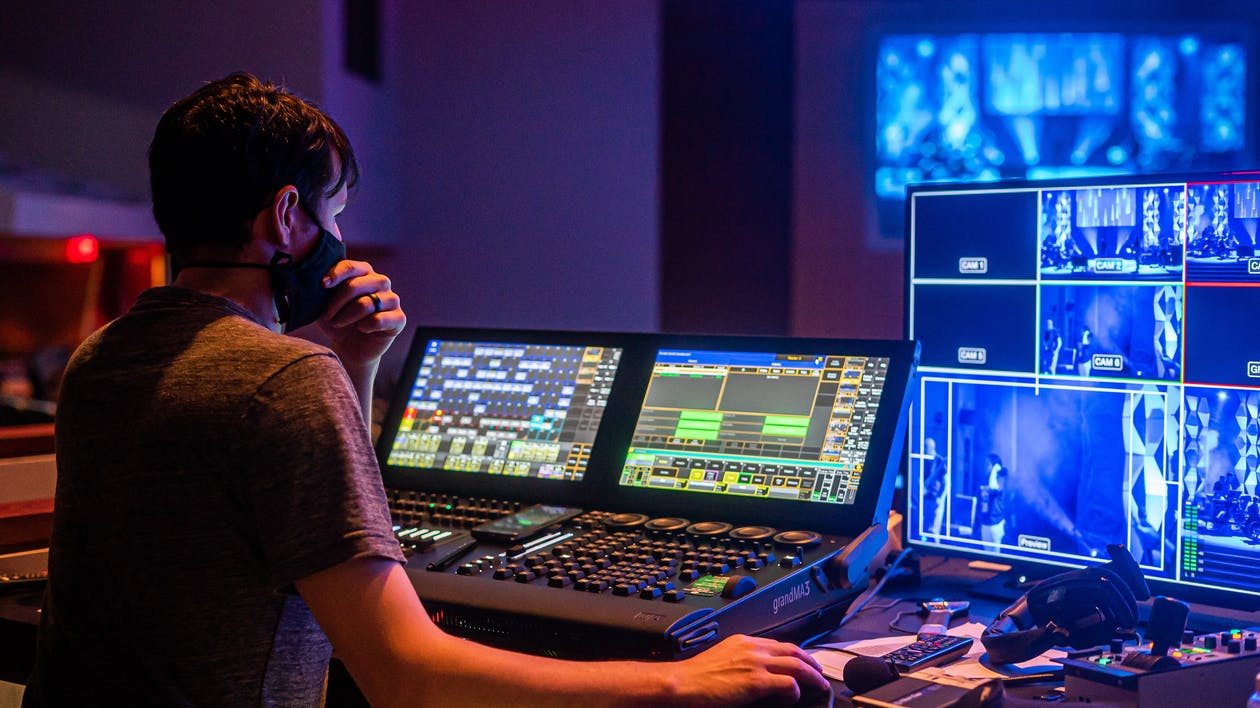 Back view of man in face mask adjusting audio and video on modern equipment during music performance
