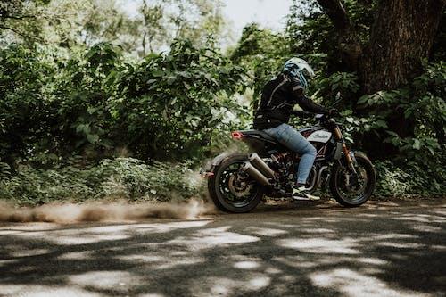 Man in Black Jacket Riding Motorcycle on Dirt Road