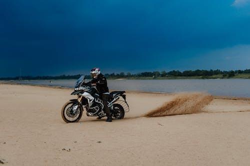 Man Riding Black and White Motocross Dirt Bike on Brown Sand