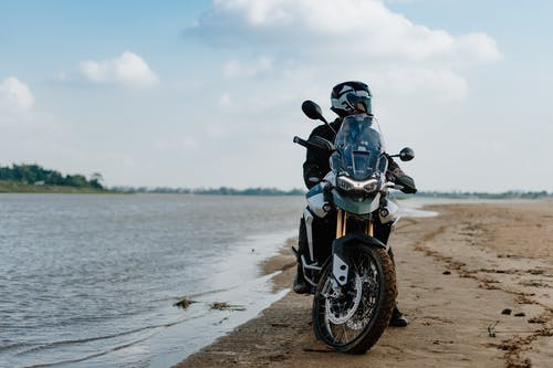 Man in Black Jacket Riding Motorcycle on Beach