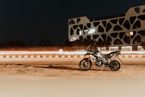 Black and Gray Motorcycle Parked Beside White and Black Wall
