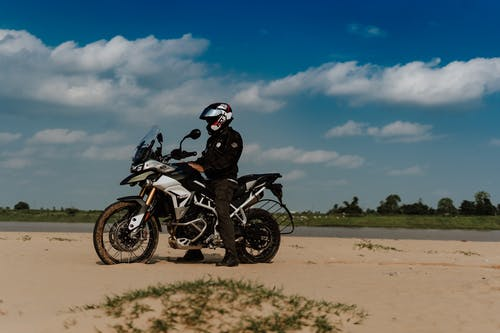 Black and White Sports Bike on Brown Sand Under Blue Sky