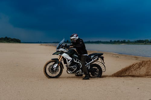 Man Riding Black and White Motorcycle on Brown Sand