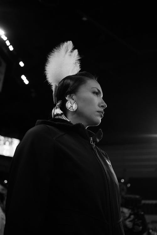 Black and white side view of female in earrings wearing headdress with white feather standing on street with glowing lamps
