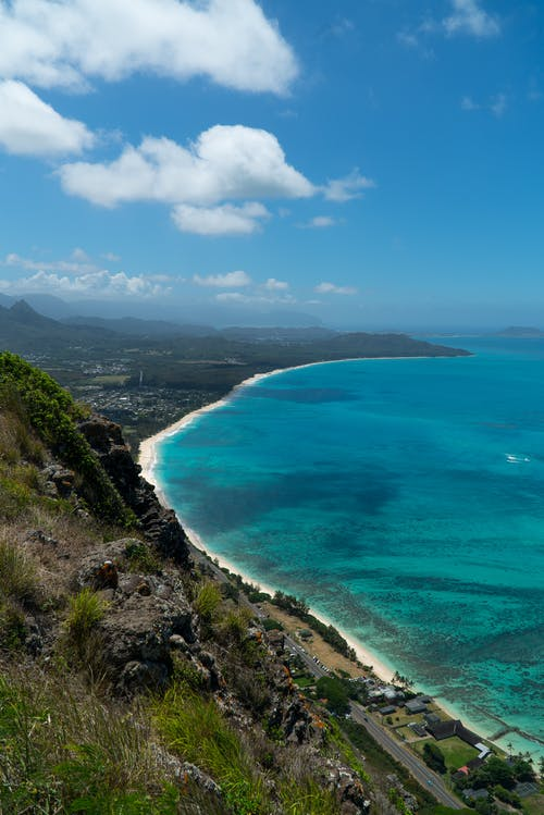 From above of azure ocean rolling near shore with mountain slope against cloudy sky in summer in tropical lagoon on nature