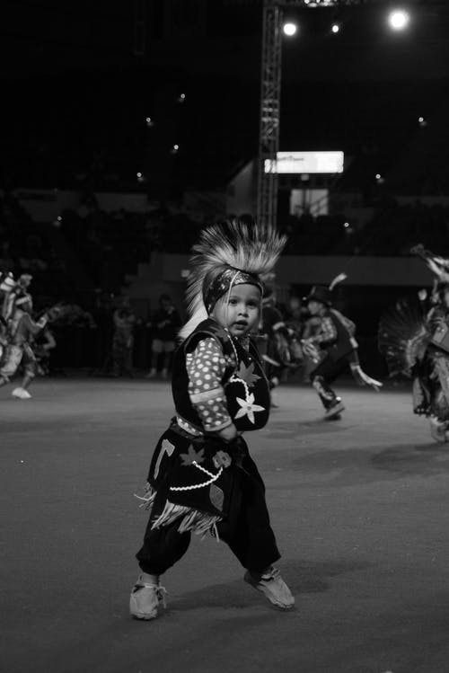 Artistic kid in traditional costume dancing on street