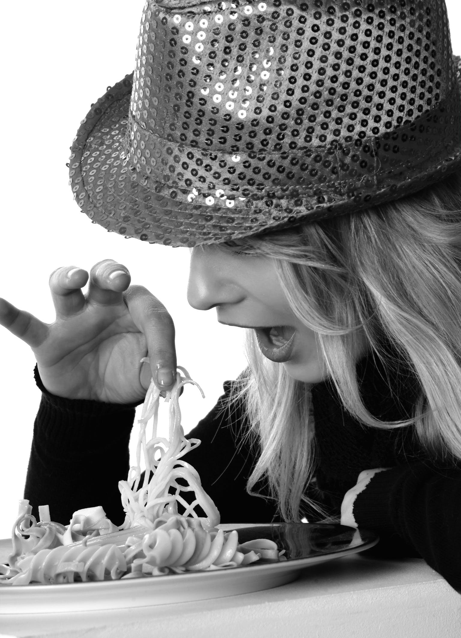 Woman in Sweater and Sequin Fedora Hat Holding Noodles in Grayscale Photography