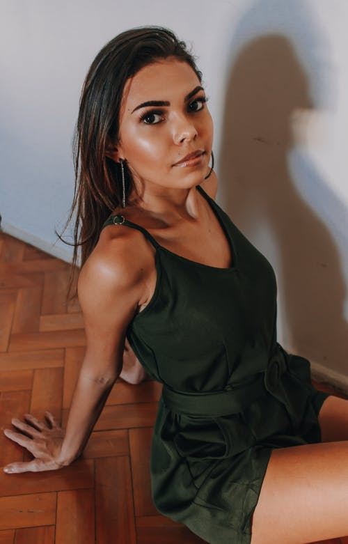 Beautiful Woman in a Green Jumpsuit Sitting on a Wooden Floor