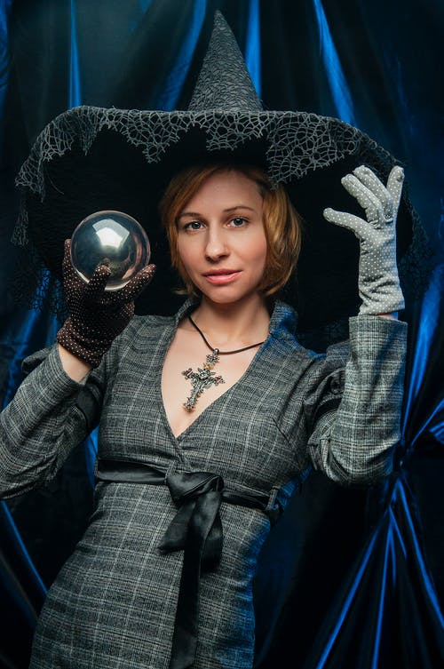 Young woman wearing witch clothes demonstrating small crystal ball while standing against blue background and looking at camera