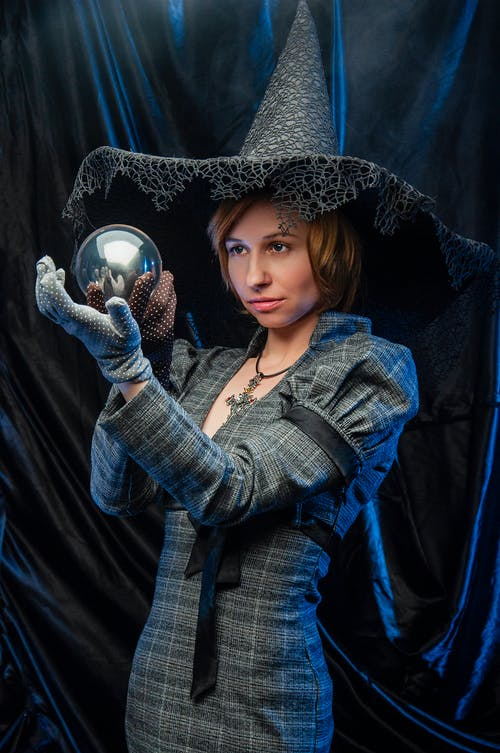 Young lady in glows and witch hat looking at magic ball