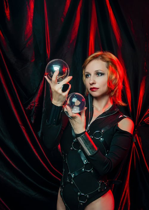 Young woman wearing witch costume with short hair looking at magic balls while standing on dark background with red illumination
