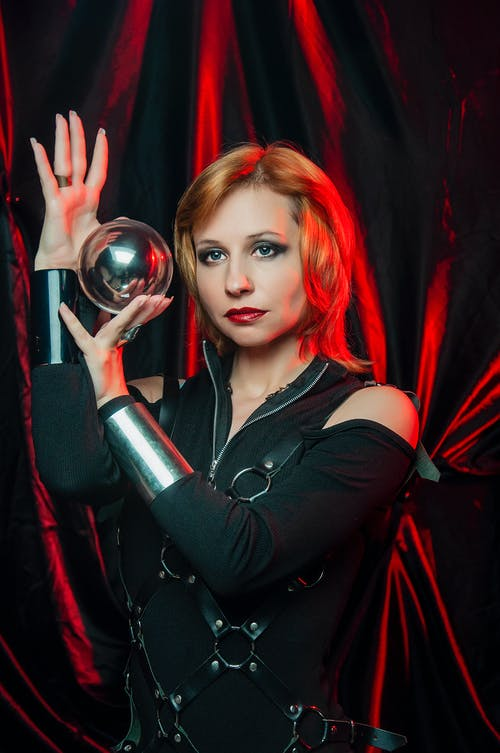 Young woman in spooky costume balancing glass ball in red light