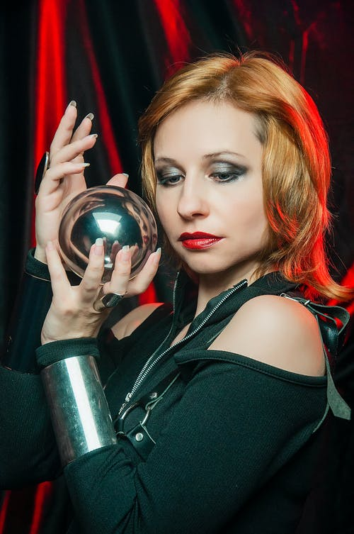 Young lady wearing black outfit with metal bracelets showing shiny ball with reflections while standing in red mystic light