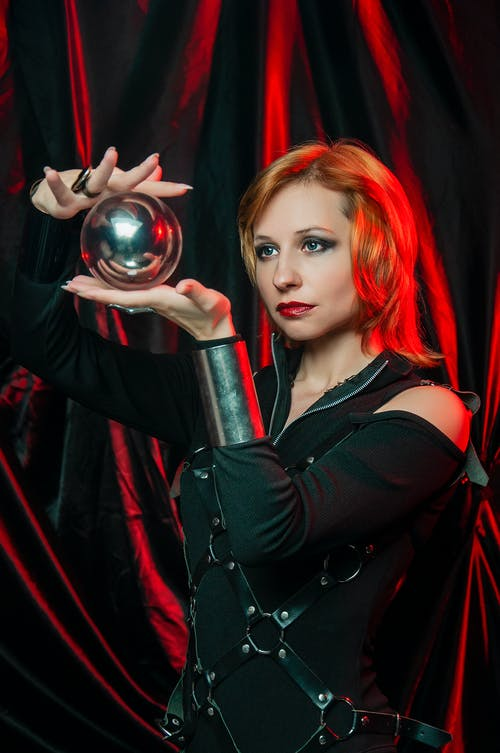 Female in Halloween costume looking at shiny ball in red light