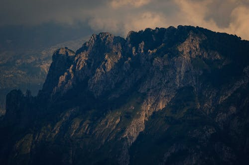 Magnificent view of rough mountain range with stiff sharp slopes located in foggy highlands in early evening