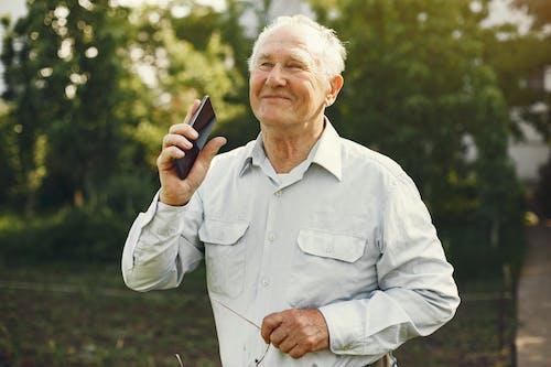 Smiling Elderly Man Holding a Cellphone