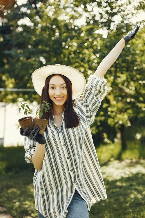 Beautiful Woman Smiling while Holding Potted Plants