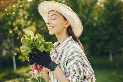 Woman In Stripe Shirt Wearing Brown Hat Holding Radish