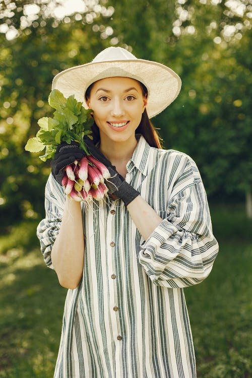 Woman In White And Black Stripe Dress Shirt Wearing Brown Sun Hat Holding Radish