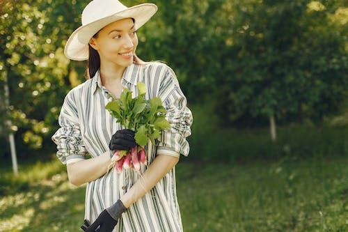Woman In Stripe Dress Shirt Holding Radish