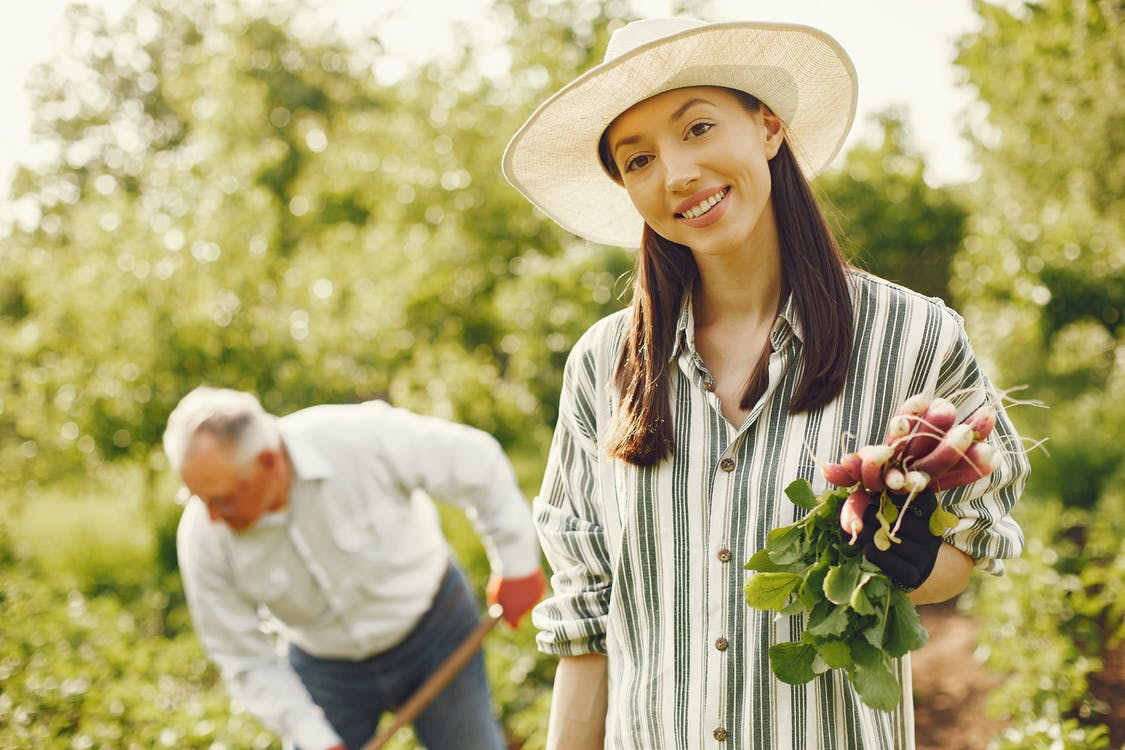 Woman In White And Black Striped Button Up Shirt Holding Radish